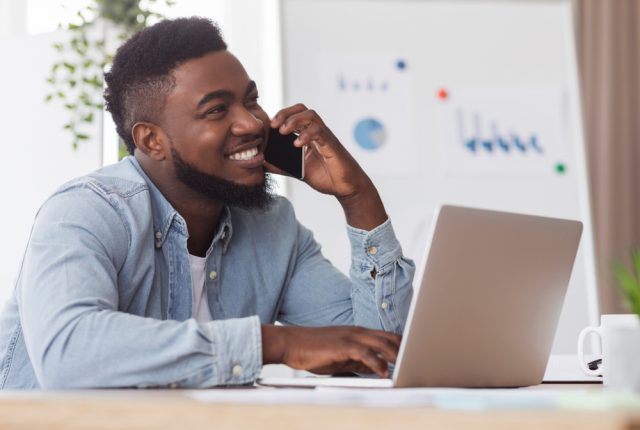 Cheerful man sat in front of his laptop and speaking on the phone