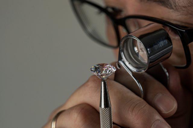 Man examining a diamond through magnifier