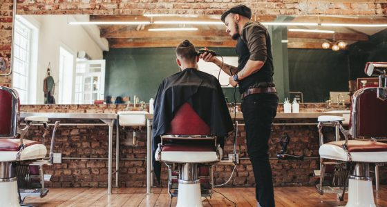 Barber cutting a mans hair in the barbers chair