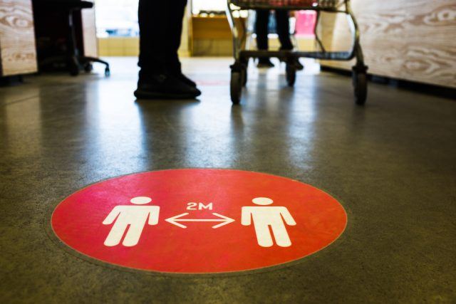 Red floor marker stating to keep 2 metres apart