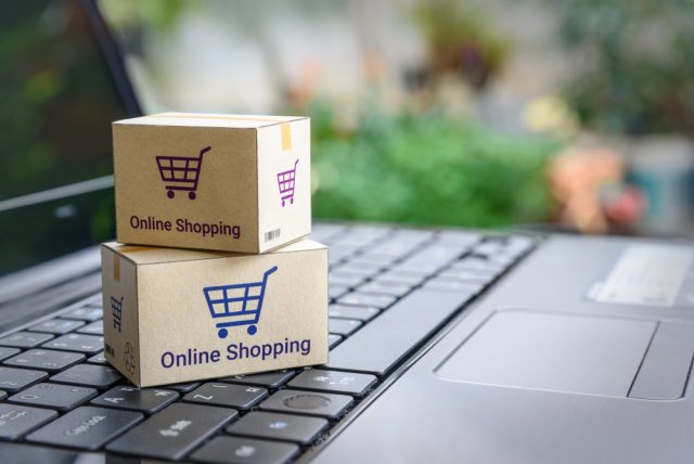 Cardboard boxes with online shopping written on the packaging placed on a laptop