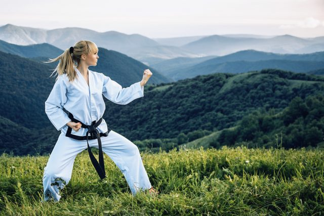 Young girl with a black belt performing martial arts in the mountains