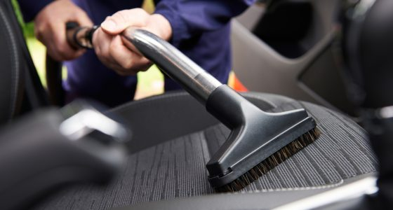 Man hoovering passenger seat of a car