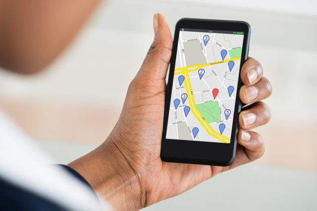 Close up of a woman holding her phone and checking maps