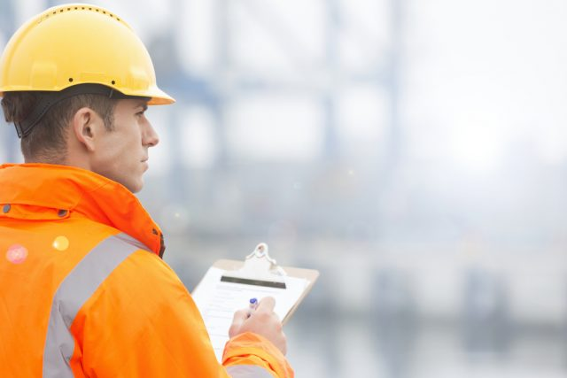Man dressed in a high visibility jacket and a hard hat using a clipboard