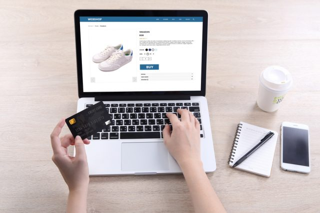 Woman entering bank card details to purchase shoes online