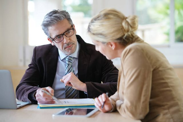 Male business man discussing with female colleague about a document
