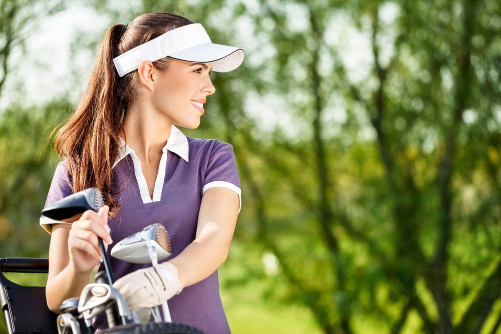 Golfer taking golf clubs out of her golf bag