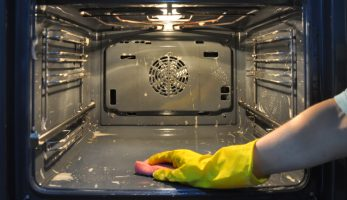 Man with yellow rubber gloves scrubbing the inside of an oven