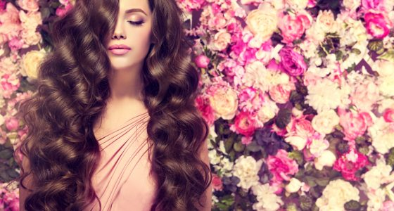 Brunette girl with wavy hair standing in front of floral background